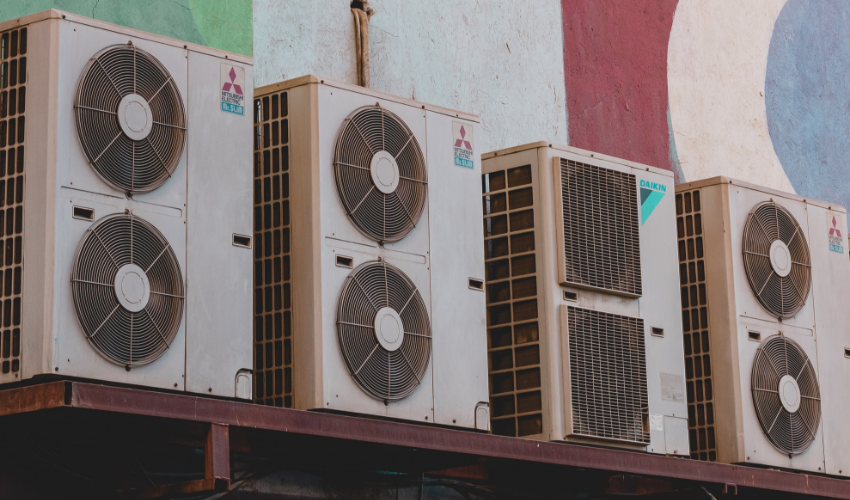 Exterior shot of air conditioning units against colourful wall
